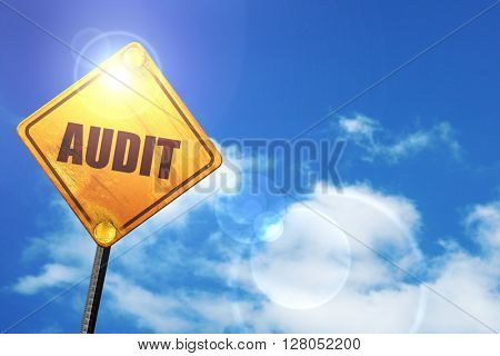 Yellow road sign with a blue sky and white clouds: audit