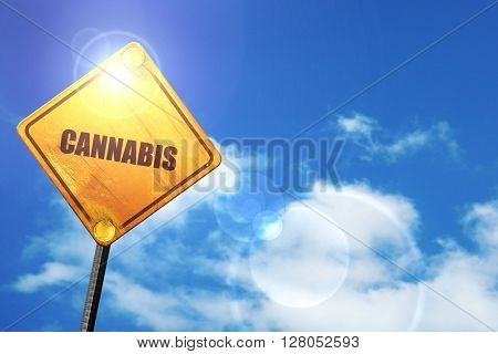 Yellow road sign with a blue sky and white clouds: cannabis