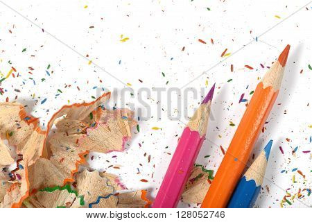Closeup of colored pencils and its shavings. Workplace of designer. Working material. Sharpening pencils. Willingness to work.  Design scene.