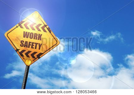 Yellow road sign with a blue sky and white clouds: Work safety s