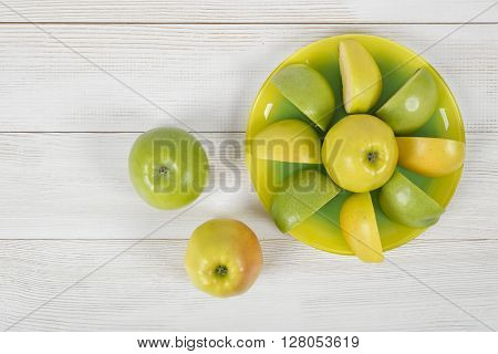 Top view of juicy yellow and green apples placed around the whole apple on a saucer. Table decoration. Healthy food. Improving health. Beating diarrhea and constipation. Boosting immune system. Natural source of iron for anemia.