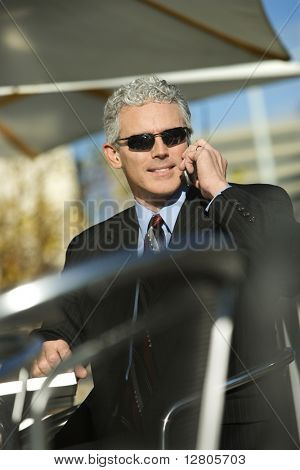 Prime adult Caucasian man in suit sitting at ouside patio table wearing sunglasses and talking on cellphone smiling.