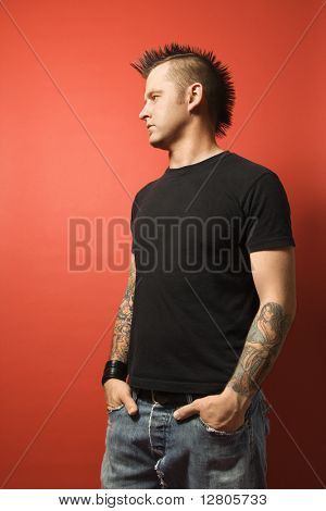 Caucasian man with mohawk and tattoos standing with hands in pockets against orange background.