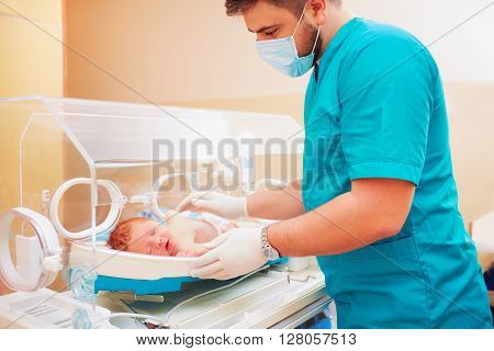 Medical Staff Taking Care Of Newborn Baby In Infant Incubator