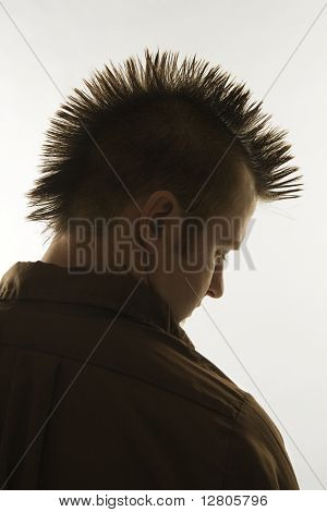 Profile of Caucasian man with mohawk against white background.