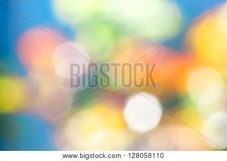 Abstract blue background with blurry yellow red white green spots