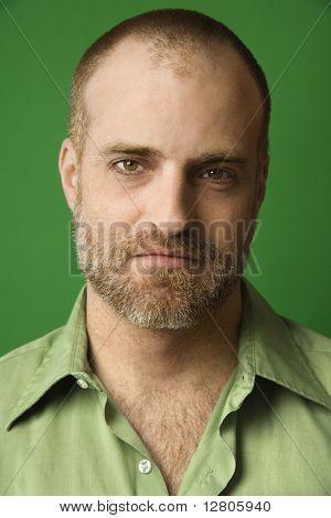 Kopf und Schulter Porträt des kaukasischen Mann mit Geheimratsecken und Bart gegen grüne backgroun