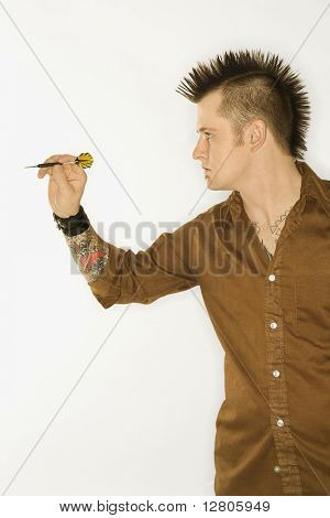 Side view of Caucasian man with mohawk holding and aiming dart against white background.