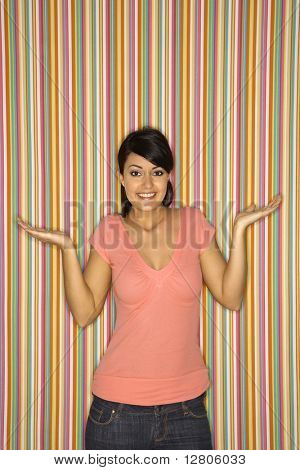 Young adult female Caucasian shrugging on striped background.