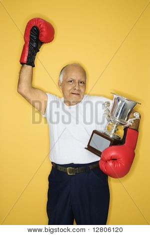 Caucasian mature adult male holding trophy and wearing boxing gloves.