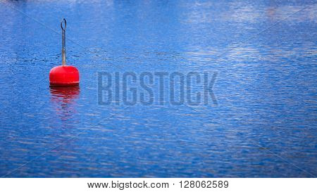 Single red buoy on calm blue sea water surface