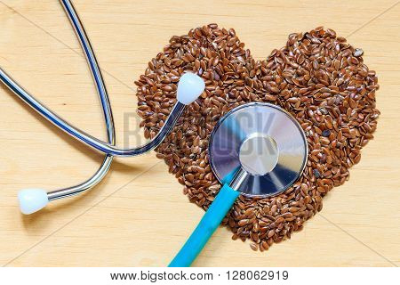Diet healthcare and checkup concept. Raw flax seeds linseed heart shaped and stethoscope. Healthy food for preventing heart diseases.