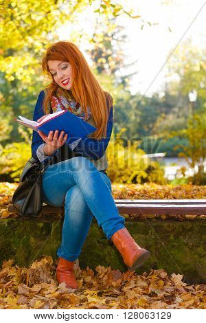 Nature people autumn concept. Ginger hair girl is reading book in park. Leaves are surrounding lady.