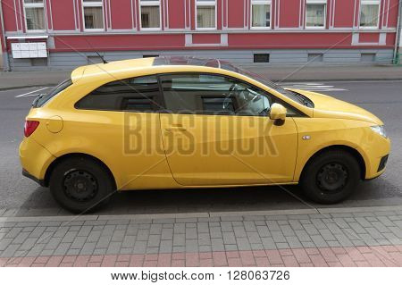 KOETHEN GERMANY - CIRCA MARCH 2016: yellow Seat Ibiza car parked in a street of the city centre