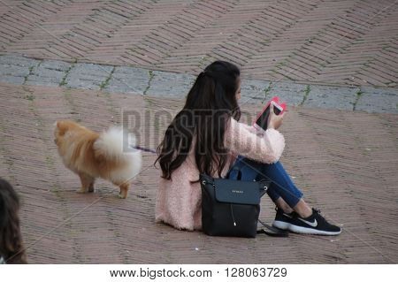 SIENA ITALY - CIRCA APRIL 2016: unidentified girl with a dog sitting and checking her smartphone