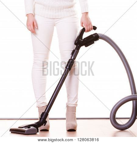 Woman vacuuming the house. Female legs with vacuum cleaner. Housework