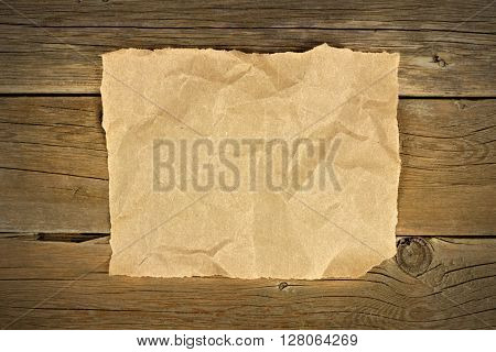 Blank Crumbled Brown Paper On A Rustic Wooden Background