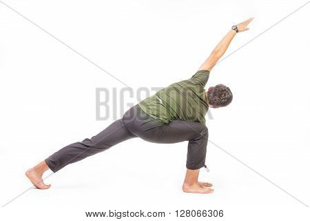 Back of a sportive barefoot fit man doing yoga exercise