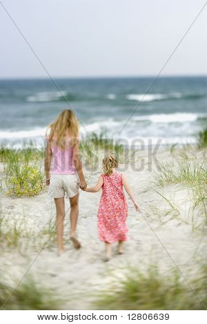 Caucasian pre-teen girl holding hands with younger Caucasian girl walking toward beach.