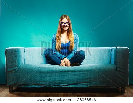 Fashion young woman in full length. Fashionable girl wearing denim sitting on couch blue background