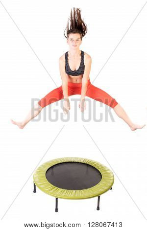 Closeup of a woman jumping and doing fitness using a trampoline - isolated on white.