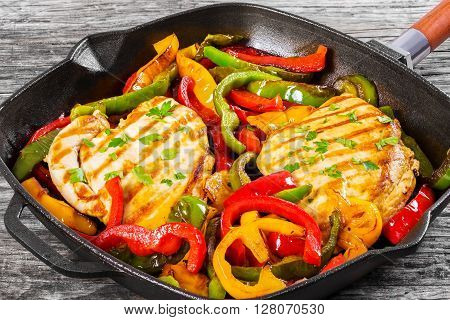 Delicious Grilled Strip Chicken breast fillet and fried bell pepper on a cast-iron skillet on an old rustic table close-up