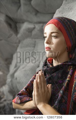 Portrait of Caucasian young adult woman wearing scarf over head holding hands to chest in prayer position.