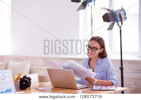Pleasant work. Cheerful charming smiling woman  sitting at the table and working with papers while expressing gladness