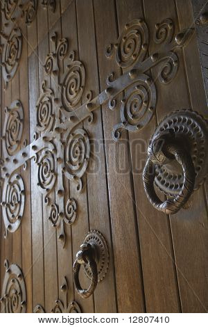 Close-up of wooden doors with decorative metalwork in Lisbon, Portugal.