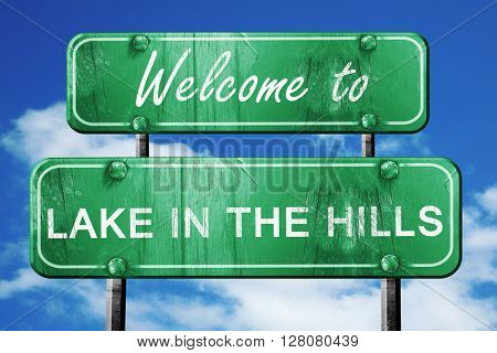 lake in the hills vintage green road sign with blue sky backgrou