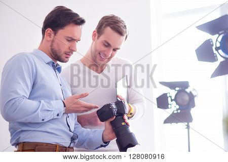 Look at this photo. Pleasant serious handsome man holding photo camera and showing it to his positive colleague while being involved in work