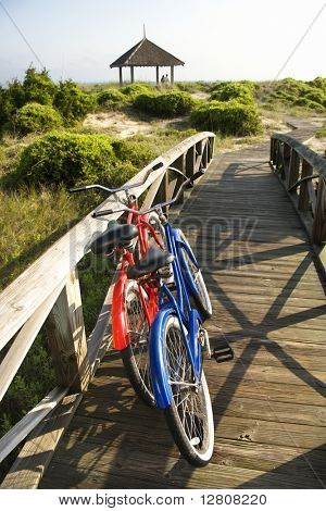 Image of red and blue bike leaning against railing of boardwalk.