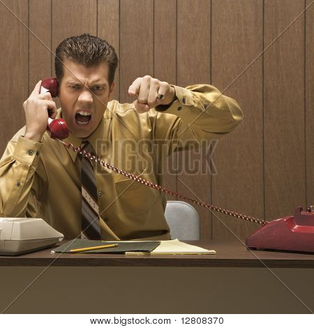 Caucasion mid-adult retro businessman sitting at desk talking on telephone with angry expression and gesture.