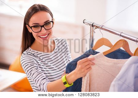 On the edge of happiness.  Pleasant overjoyed beautiful woman smiling and choosing clothes while being involved in work