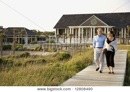 Caucasian mid-adult couple walking on walkway near beach home.