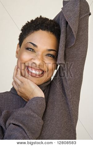 Close up of African- American woman with head on hand looking at viewer smiling.