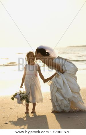 Caucasian mid-adult bride kneeling to give flower girl a kiss on the cheek while holding hands barefoot on beach.
