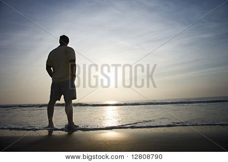 Caucasian mid-adult man standing alone on beach looking at ocean at sunrise.