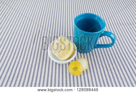 An overhead close up shot of hot lemon water in a blue coffee cup