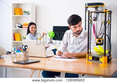 Proceed working.  Pleasant handsome concentrated man using 3d printer and making notes while his colleague smiling in the background