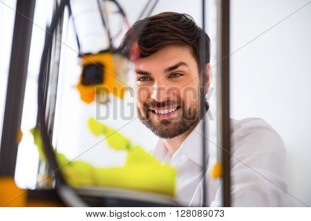 Do it with pleasure. Cheerful delighted smiling man using  3d printer and expressing gladness