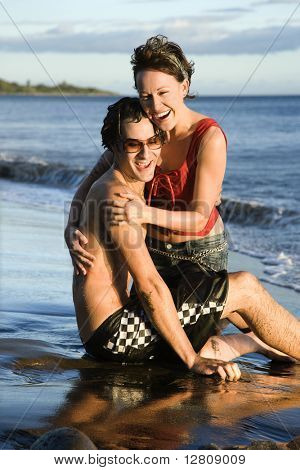 Caucasian young adult couple frolicking on beach.