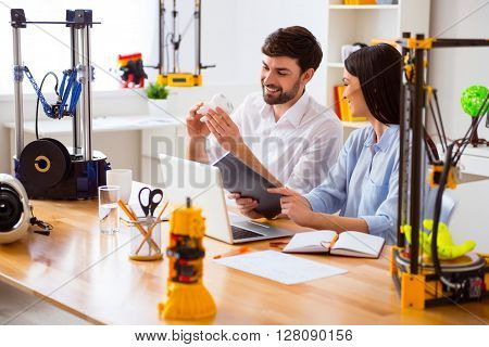 In a good mood. Cheerful  pleasant smiling colleagues sitting at the table  and holding model printed on the 3d printer while working together