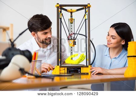 Nice operation.  Cheerful delighted smiling colleagues sitting at the table and looking at the 3d printer while expressing positivity
