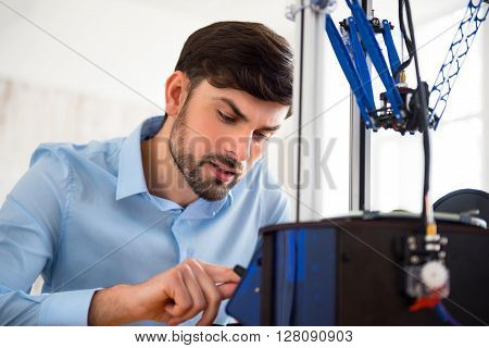 A real professional.  Pleasant concentrated man sitting at the table and using 3d printer while being involved in work
