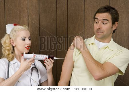 Caucasian mid-adult female nurse giving shot to man with oversized syringe.
