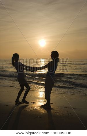 Caucasian mid-adult mother and teenage daughter holding hands spinngin on beach at sunset.