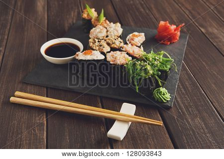Japanese food restaurant, sushi gunkan roll plate, platter set. Creative food. Set with chopsticks, ginger, soy, wasabi. Sushi at rustic wood background and black stone. POV, horizontal image