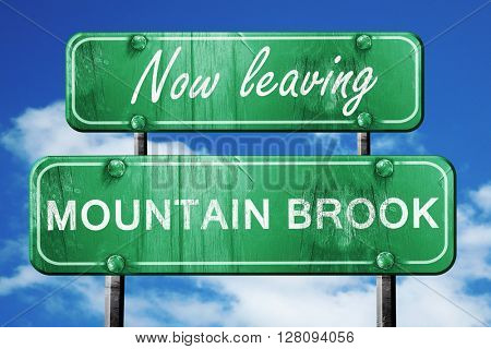 Leaving mountain brook, green vintage road sign with rough lette