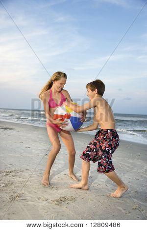 Kaukasische pre-teen jongen en meisje te trekken op beachball.